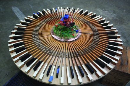 This piece reconfigures the well known solo instrument into a circular and group playing device. All materials were salvaged from the San Francisco dump including a working ibook computer, upright piano parts and a dell computer keyboard micro-controller. (Photo credit: Micah Gibson)